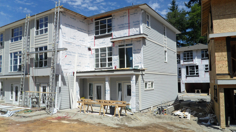 From the back yard view, our unit # 6 at the end with siding almost complete.  At grade is patio with main entrance door on right and flex entrance on left; deck on 2nd floor off kitchen sliding doors and master bedroom on third.  Bruce's unit # 4 immediately to left of ladders.