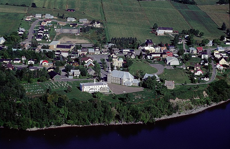 This view of Deschambault looking north over the St. Lawrence River shows the situation of the town: on a bluff above a cliff along the river (the cliff face is mostly obscured by trees). The park mentioned earlier can be seen just to the right of center, with two flag poles and several benches, along the cliff-edge.