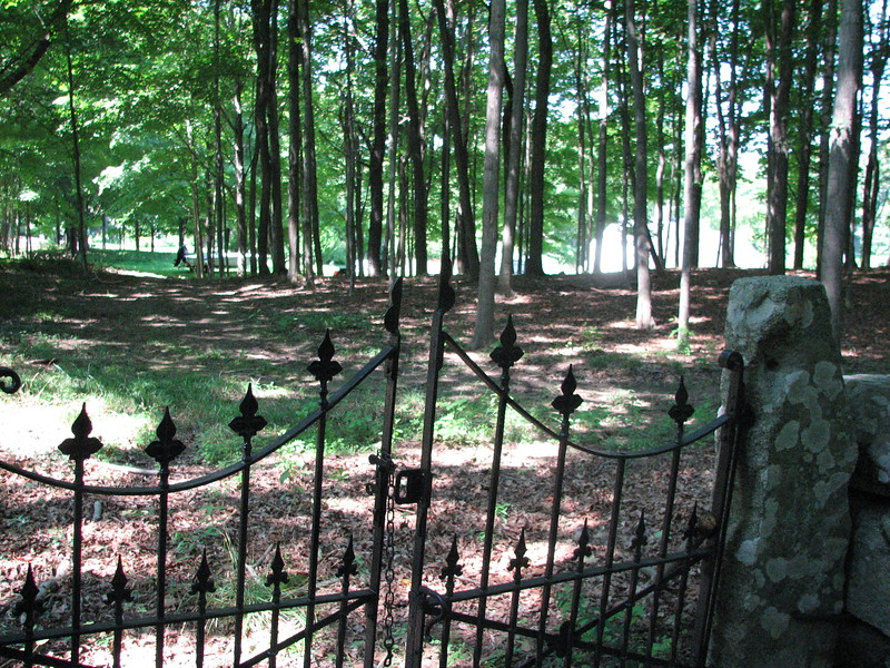 Looking out of the cemetery gate toward the road. The Sullivan house is seen (overexposed in this photo) in the right distance.