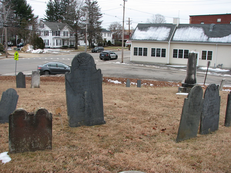 Baldwin's stone is the large dark one in left-center. Use this photo to help locate the grave. North Main Street is in the distance, with Maple St between the cemetery and the beige building. The grave is about 70 feet from Maple St, and 60 feet from North Main St.