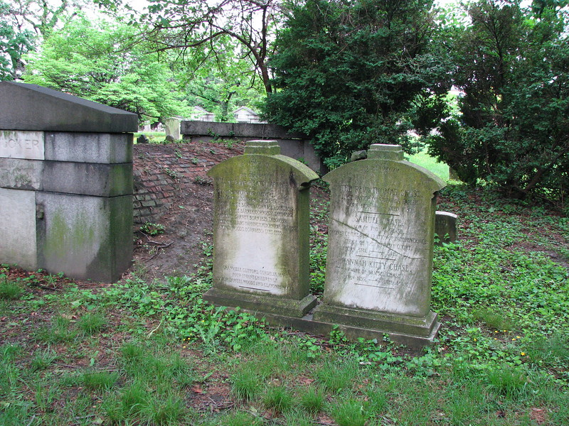 The stone on the right is that of Chase. Older photos show crosses atop these twin stones. To locate the grave, walk straight in from the main gate about 100 feet and the stone will be on your right.