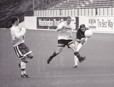 Zane Higgins (R) shoots as midfielder Kris Hollingshead (C) and defender Joe Marks (L) challenge.