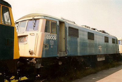 A weather beaten and washer stained 83009 stands at Crewe Electric Depot on 22 July 1989.