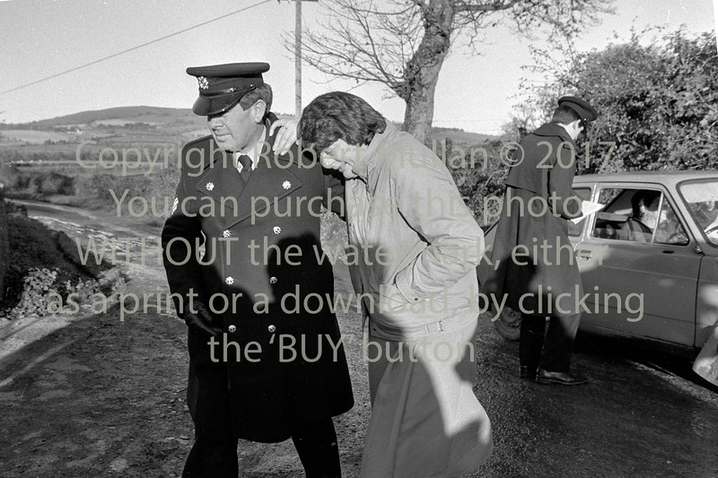 Sgt Des Kidney comforts a neighbour of Margaret Nolan who along with her daughter Anne was found murdered at their home in Kilbride.  Date 1986