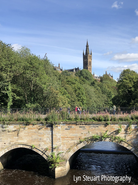View over the bridge on Kelvin river with University of Glasgow Bell tower in the background