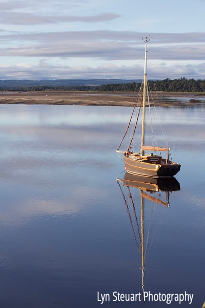 Sailboat on the still waters of Findhorn Bay in the early morning.