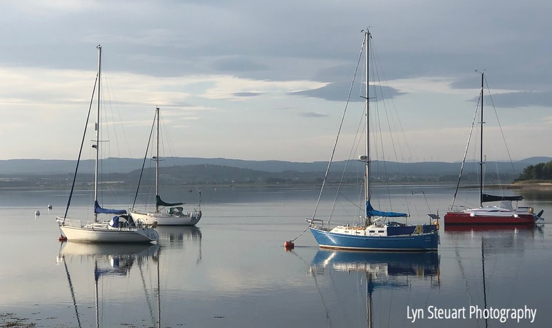 Early morning and the sailboats float on the quiet waters of Findhorn Bay