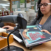 Fitchburg Childrens Library Assistant Meilynn Santiago, 19, checks book backs in after they have been returned on Thursday, July 20, 2017.  SENTINEL & ENTERPRISE/JOHN LOVE