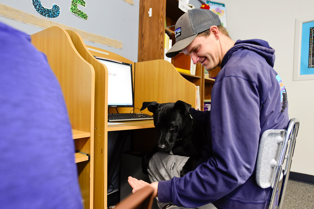 . Josh Volf plays with Rumba at Crossroads School in Longmont, Colorado on Nov. 10, 2017. Volf was adopted at age 11 from Ukraine. At 19, Volf has now returned to school and is planning to graduate in May. (Photo by Matthew Jonas/Times-Call)