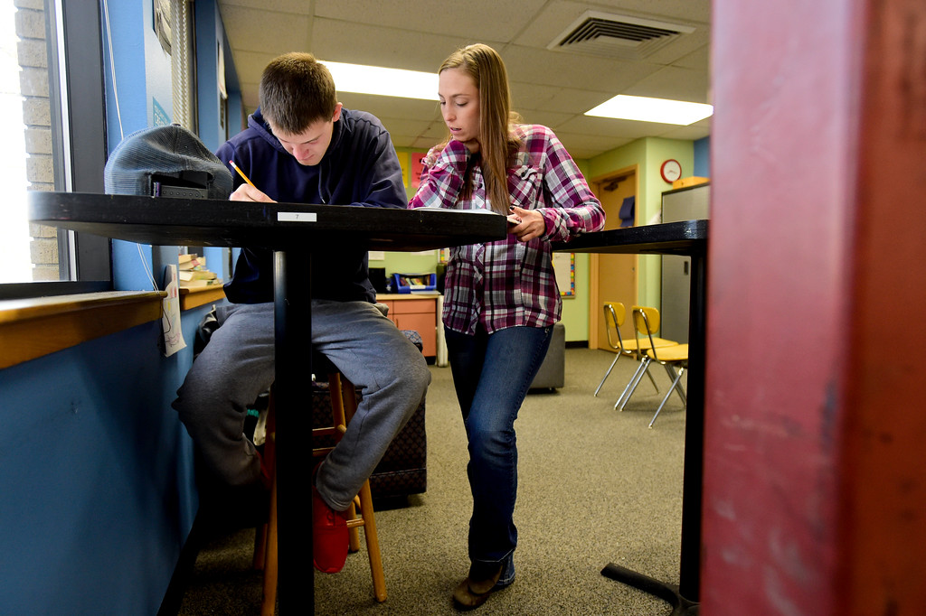 . Josh Volf works on an assignment as English Teacher JamieLee Szalaj looks on at Crossroads School in Longmont, Colorado on Nov. 10, 2017. Volf was adopted at age 11 from Ukraine. At 19, Volf has now returned to school and is planning to graduate in May. (Photo by Matthew Jonas/Times-Call)