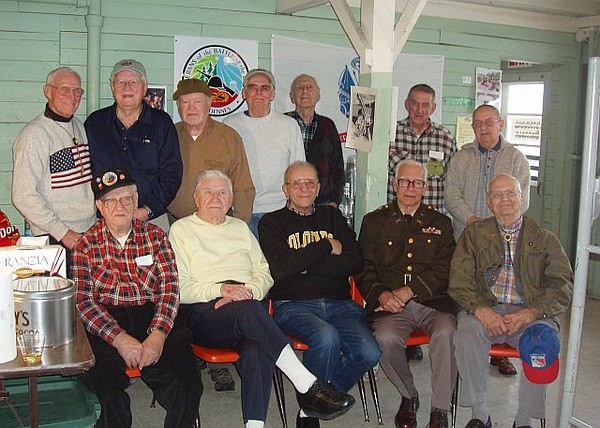 Here are three 87th Division Veterans attending the re-enactment:<br /> <br /> In top row extreme left; <br /> with American Flag on sweater, George Watson; M-346;<br /> In brown shirt and wool knit cap; John McAuliffe; M-347<br /> In front Row, extreme right: Charles Nelson, M-346.<br /> <br /> We lived in the original WW-II barracks as you can see....<br /> Lots of Fun and memories..<br /> <br /> photo and info submitted by <br /> John McAuliffe
