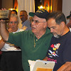 L-R foreground Joe Basso 60-62 holds up commemorative plaque that is to be raffled off at the dinner on Saturday night while Tom Planes 59-60 checks through his notes to be sure that we have made reservations for dinner.