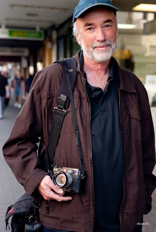 Photograph by Wallace Chapman<br /> <br /> MAN WITH A CAMERA<br /> <br /> It's quite amazing considering the number of cameras sold and blogs around, just how few a number of people focus on street photography in any serious capacity. I bumped into a maestro of street photography in Wellington. His name is Julian Ward and has been taking mainly b&w images from around the city for many many years. Julian uses the same type of camera that I do..an M leica - digital and film. Check his top work and his book in the link.