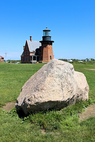 After raising almost $2 million in private and Federal funding in August 1993 the lighthouse and dwellings were raised with hydraulic jacks and moved 300 feet back away from the bluff.   The boulder marks the original location of the lighthouse.
