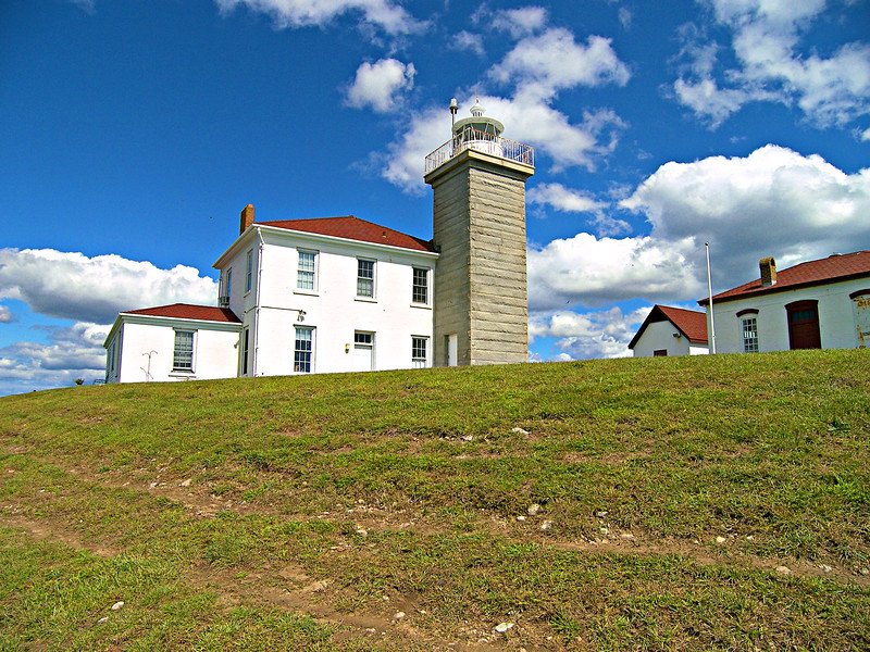 The government purchased four acres of land at Watch Hill Point for $500 in 1806.  A 35 foot tall wooden tower was constructed at the point by Elisha Woodward of New London, CT in 1807.  A one story home was also built for the Keeper Jonathan Nash.  Nash would serve at the Watch Point Light for 27 years.