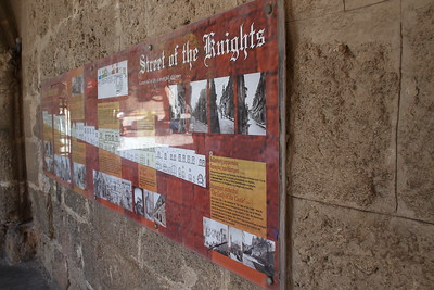 Plaque commemorating the Street of the Knights, arguably the most important street in Rhodes Old Town.  The Street of the Knights was home from the 14th century to the Knights Hospitaller who ruled Rhodes. They were divided by birthplace into seven 'tongues', or languages – England, France, Germany, Italy, Aragon, Auvergne and Provence – each responsible for a specific section of the fortifications. As this sign explains, the street holds an 'inn', or palace, for each tongue.