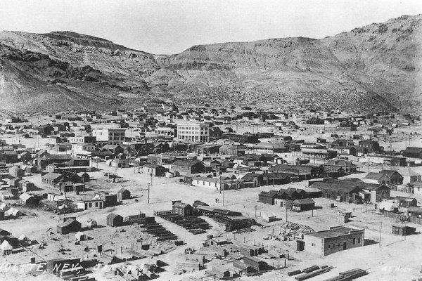 Historical photo of Rhyolite as it appeared at it's peak, around 1908. In it's day, Rhyolite had a population of over 8,000 people, 3 water systems, 3 train lines, telephone and telegraph offices, electricity, over 50 mines, 3 newspapers, an opera house, a symphony, baseball teams, tennis courts, 3 public swimming pools, 2 undertakers, 3 hospitals, 8 doctors, 2 dentists, 19 hotels, 18 grocery stores, 53 saloons, a catholic and presbyterian church and an extensive red light district.