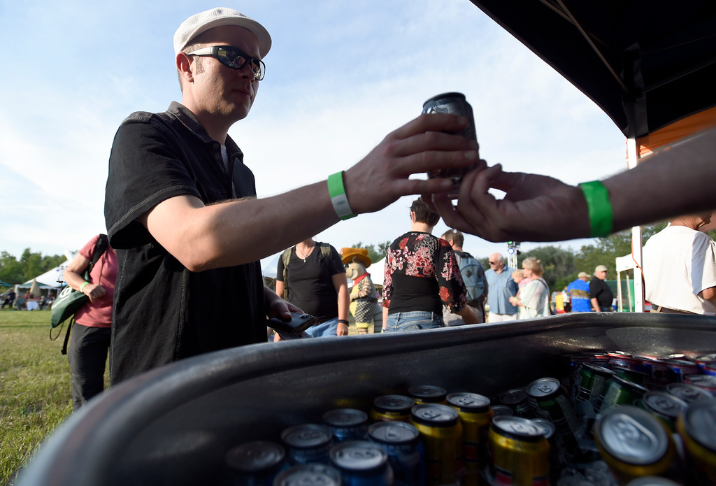 . Matt Grundstad grabs a beer from the Oskar Blues Brewery tent during the Rhythm on the River on Friday in Longmont. For more photos of the event go to www.dailycamera.com Jeremy Papasso/ Staff Photographer/ July 7, 2017