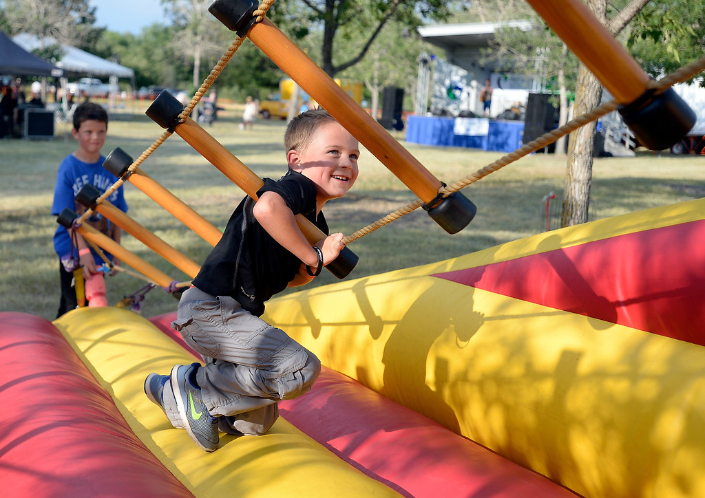 . Dreyson Blase, 6, tries to climb the Jacobs Ladder while his brother Jaxson, 8, at left, waits his turn during the Rhythm on the River on Friday in Longmont. For more photos of the event go to www.dailycamera.com Jeremy Papasso/ Staff Photographer/ July 7, 2017