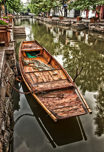"""I am going to quote the guide book. This photo of a Water Taxi was taken in the """"Zhujiajiao Water Town is situated forty seven kilometers away from Shanghai. It is a typical and ancient water town in Qingpu District, south of the Yangtze River, which has almost 1,700 years of history. Zhujiajiao, also called """"The Venice of Shanghai"""", features lovely waterways, curved rock bridges, old streets cemented with stone, and over 10,000 buildings dating back to the Ming (1368-1644) and Qing dynasties (1644-1911)."""" If you have an opportunity to visit Shanghai this is worth the trip to visit this village."""