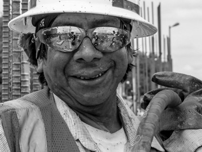 Cement Man, he does have a name, but on this day he was splattered with cement and sweat on his face. If you look carefully in the right hand lens of the sunglasses you will see me shooting the photo. Reflections are a great way to get into a photography and place you on location.  My friend is a fellow with a happy face who does a number of different task on the job.
