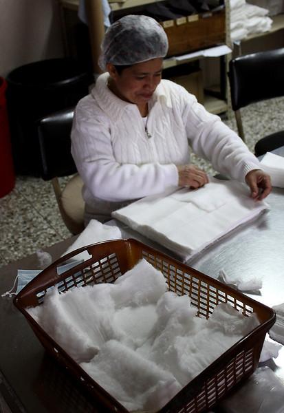 Here is a nurse working at hand folding four by four gauze pads, which were cut on the machine above.