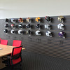 Carol Harper — The Morning Journal <br> A wall of helmets from each National Football League team misses eight helmets taken to another room for visitors to view at the Riddell open house.