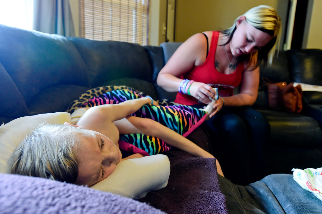 . Erin uses a pulse oximeter to test oxygen levels in Riley\'s blood at their home in Mead, Colorado on June 27, 2018. Riley has Pantothenate Kinase-Associated Neurodegeneration, also known as PKAN, a rare nerve disease which causes iron to accumulate in the brain. (Photo by Matthew Jonas/Staff Photographer)