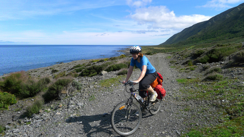 Nora cycling the coast on from Turakirae Head.