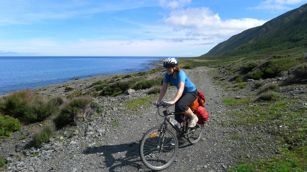 Nora cycling the coast on from Turakirae Head.