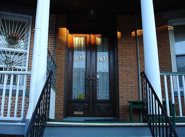 The doors retain a pristine quality, having been protected over the decades from the elements by the porch roof.  2005.