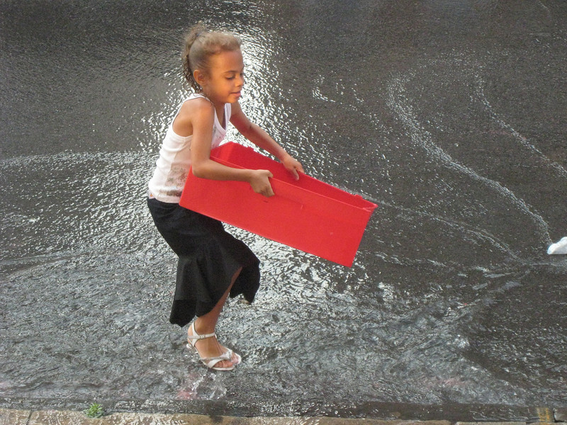 A neighborhood girl frolics in an artificial brook, thanks to a fire hydrant.  She is set off by a chance halo created by an effect of reflected light.