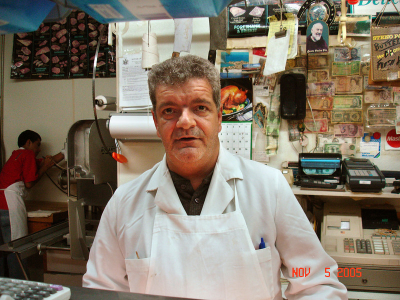"Vinnie the butcher.  Over his left shoulder is a picture of ""Beato Padre Pio"" (now ""<i>San</i> Padre Pio"")."