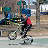 """The playground equipment at Joanne """"Mama"""" Fitz Memorial Playground in Fitchburg was still off limits to play on during the coronavirus emergency Thursday, March 26, 2020. That did not stop Danielle Moriarty from bring her son Dillon, 8 pictured, and her granddaughter Taytum Emery, 4, to the park to ride their bikes on the basketball court to get them out of the house. Dillon tries to show off his wheelie skills as he rides around. SENTINEL & ENTERPRISE/JOHN LOVE"""