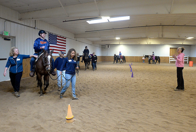 Instructor Alex Whittey, far right, leads a group Wednesday, Sept. 27, 2017, through a program called Riding in the Moment which is geared towards people with dementia, Alzheimer's Disease and other forms of memory loss, at Hearts & Horses Theraputic Riding Center in Loveland. (Photo by Jenny Sparks/Loveland Reporter-Herald)