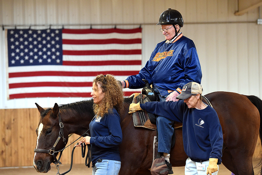 . Harry Hull rides a horse named George Wednesday, Sept. 27, 2017, with the help Christina Panasci, left, and Mary Hofer, right, while participating in Riding in the Moment, a program geared towards people with dementia, Alzheimer\'s Disease and other forms of memory loss, at Hearts & Horses Theraputic Riding Center in Loveland. (Photo by Jenny Sparks/Loveland Reporter-Herald)