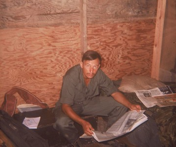 AR-14 Tony Cordia of 1st Platoon reads the newspaper in basecamp barracks