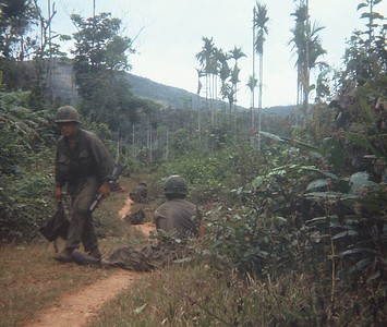 "AR-7 Gary L "" Snoopy"" Elmore moves back up the trail with his M-79 as others take a break."