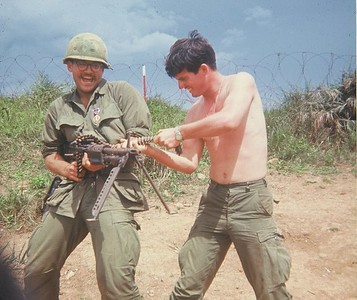 AR-18 John 'Chunky' Carlson (NJ) and John Hacker (CA) goofin' with an M-60 at some LZ