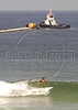 A surfer rides a wave on the Barra da Tijuca beach in Rio de Janeiro, in front of a tugboat maneuvering a section of floating sewage pipe into position where it will be submerged. Several pipe sections will be joined to form an underwater sewage line to release untreated sewage into the ocean 5.5 km from the beach. While some private condominiums in the area have their own sewage treatment plants, the majority of sewage of 500,000 people flows untreated into the nearby lagoons and eventually the ocean. The underwater line will later be connected to a sewage treatment plant and a network of underground urban sewage lines, both planned.(Australfoto/Douglas Engle)