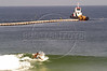 A surfer rides a wave on the Barra da Tijuca beach in Rio de Janeiro, in front of a tugboat maneuvering a section of floating sewage pipe into position where it will be submerged. Several pipe sections will be joined to form an underwater sewage line to release untreated sewage into the ocean 5.5 km from the beach. While some private condominiums in the area have their own sewage treatment plants, the majority of sewage of 500,000 people flows untreated into the nearby lagoons and eventually the ocean. The underwater line will later be connected to a sewage treatment plant and a network of underground urban sewage lines, both planned. (Australfoto/Douglas Engle)
