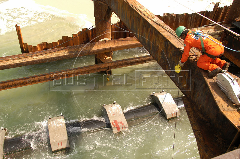 Workers help position a section of floating sewage pipe where it will be submerged, in front of the Barra da Tijuca beach in Rio de Janeiro. Several pipe sections will be joined to form an underwater sewage line to release untreated sewage into the ocean 5.5 km from the beach. While some private condominiums in the area have their own sewage treatment plants, the majority of sewage of 500,000 people flows untreated into the nearby lagoons and eventually the ocean. The underwater line will later be connected to a sewage treatment plant and a network of underground urban sewage lines, both planned.(Australfoto/Douglas Engle)