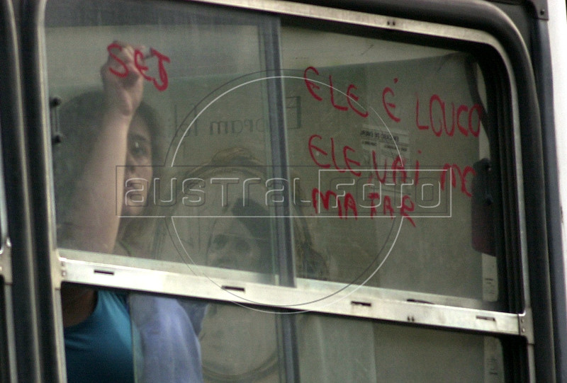 "A woman hostage writes ""he is crazy. is is going to kill me."" with lipstick on the window of a hijacked bus in Rio de Janeiro, Brazil, June 12, 2000. The bus, with 6 passengers aboard, was hijacked by Sandro do Nascimento for about 4 hours after a robbery went wrong. When he agreed to surrender, police officers attempted to shoot him but ended up killing one of the passengers. The incident, broadcast on live TV in Brazil, demonstrated the incompetence of Rio's police and shocked cariocas (Rio residents), normally accustomed to such things. The event was also immortalized by the Jose Padilha film ""Onibus 174"" (Bus 174). (Australfoto/Douglas Engle)"