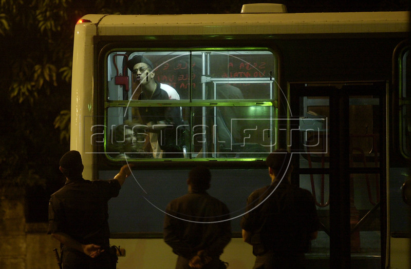"""Police try to reason with bus hijacker Sandro do Nascimento, pointing a gun at the head of a hostage, in Rio de Janeiro, Brazil, June 12, 2000. The bus, with 6 passengers aboard, was hijacked by Nascimento for about 4 hours after a robbery went wrong. When he agreed to surrender, police officers attempted to shoot him but ended up killing one of the passengers. The incident, broadcast on live TV in Brazil, demonstrated the incompetence of Rio's police and shocked cariocas (Rio residents), normally accustomed to such things. The event was also immortalized by the Jose Padilha film """"Onibus 174"""" (Bus 174). (Australfoto/Douglas Engle)"""
