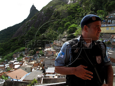A Rio de Janeiro police officer patrols near the Christ the redeemer statue in the Dona Marta Slum in the Botafogo distrct of Rio de Janeiro, Brazil. The RIo de Janeiro state police, notorious for its lack of tact with slum residents, has started a new community policing program in the community which will be implemented in other areas if successful. Drug traffickers were driven out in Dec. 2008 and new, young police recruits have taken their place as the law of the land, including permanent police posts in the slum. (Australfoto/Douglas Engle)