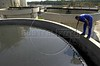 A worker maintains a tank at a sewage treatment plant in Rio de Janeiro. The plant treats sewage from 45 neighborhoods, then releases it into the Guanabara Bay 30 percent cleaner than when it received it.  The treatment plant, one of eight around the bay, is part of a program to clean up the Guanabara Bay. The bay is more representative of Rio than the tourist postcards it is famous for. Each day, the bay receives some 470 tons of raw sewage, about 10 tons of solid garbage, five tons of oil and an unknown quantity of industrial waste. (Australfoto/Douglas Engle)