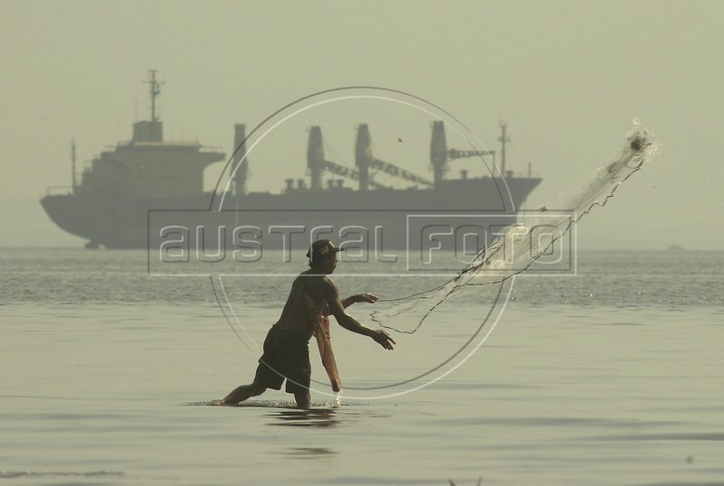 A fisherman cast his net in the Guanabara Bay of in front of an anchored cargo ship.(Australfoto/Douglas Engle)