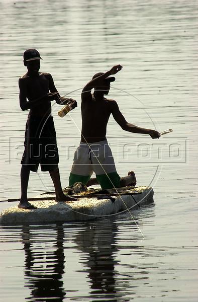 Boys fish from a piece of styrofoam in the Guanabara Bay in Rio de Janeiro.(Australfoto/Douglas Engle)