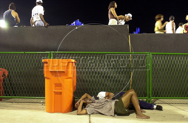 Carnival fans sleep on the ground inthe sambodrome as the Mangueira Samba School parades during carnival in Rio de Janeiro in 2001. (Douglas Engle/Australfoto)
