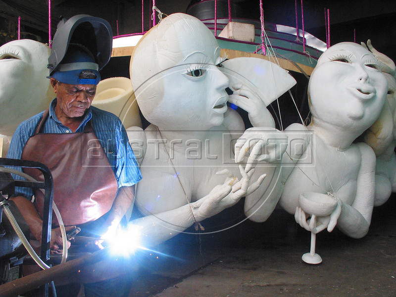 """A worker at the Grande Rio Samba school welds on an allegorical float under construction in Rio de Janeiro, Brazil. The Catholic Church has criticized the school , which has chosen the theme of """"Use a condom my Love"""" for several pieces of their parade this year. (Douglas Engle/Australfoto)"""